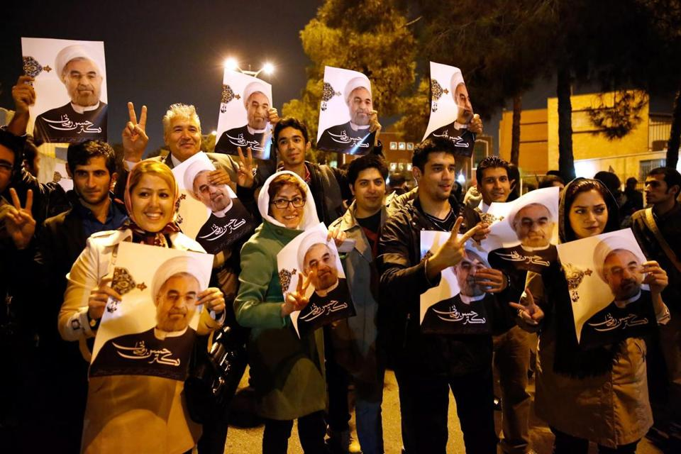 Supporters of Iranian President Hassan Rouhani held portraits of him as they waited to welcome the negotiators arriving from Geneva.