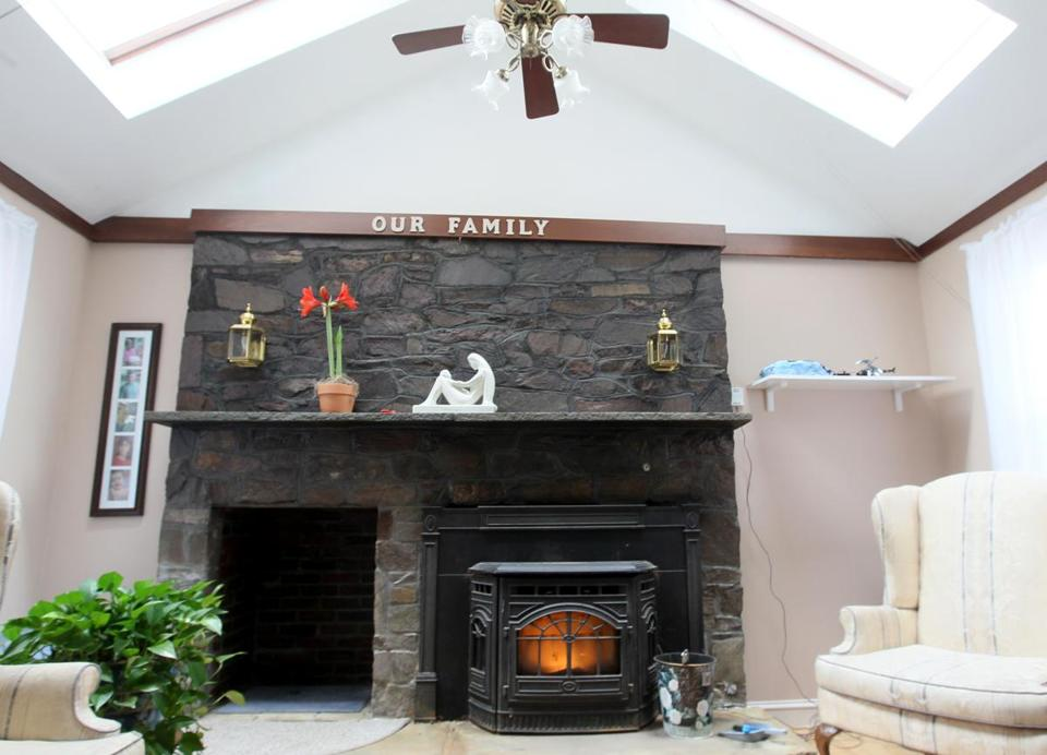 The living room features a fireplace with a large stone wall serving as a dramatic mantel and a pellet stove insert.