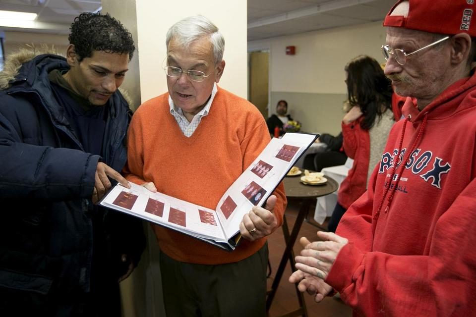At St. Francis House shelter in Boston, Raul Davila (left) showed Mayor Menino a book of pictures, while Mark Morrissey (right) applauded.