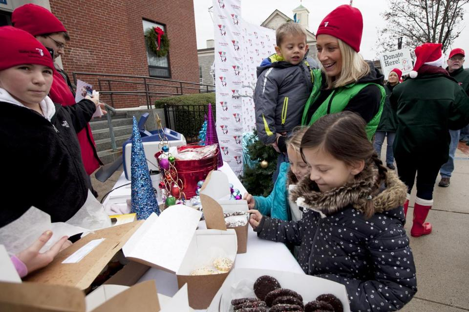 Kerri Delaney, owner of Babycakes, held Jack Carthas, 3, as she watched Camryn, 5, and Kaleigh Carthas, 7, pick a treat after posing for a photograph with Santa at a Globe Santa event in Quincy on Sunday. At left is Taylor O'Connor, 10.
