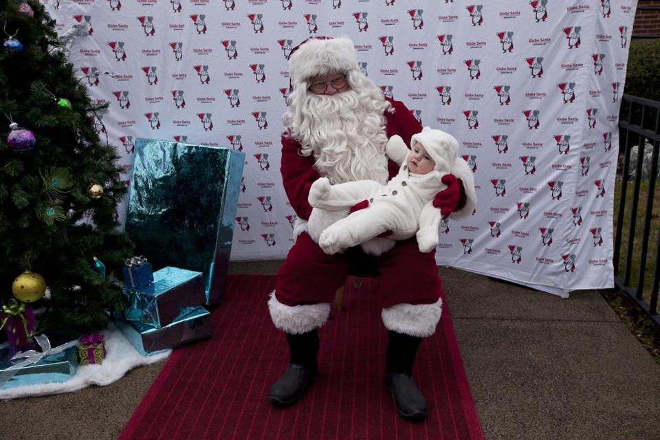 Santa held 7-month-old Naya Donovan of Marshfield at a Globe Santa event in Quincy with Mayor Tom Koch.