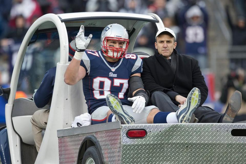 Rob Gronkowski, riding with Dr. Thomas Gill, waves as he's carted off the field after injuring his knee. He was taken to the hospital Sunday and was expected to have an MRI Monday.