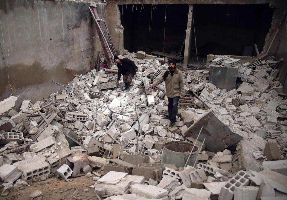 People walked on debris of damaged buildings at a site hit by what activists say was shelling by forces loyal to Syrian President Bashar Assad in  Damascus on Wednesday.