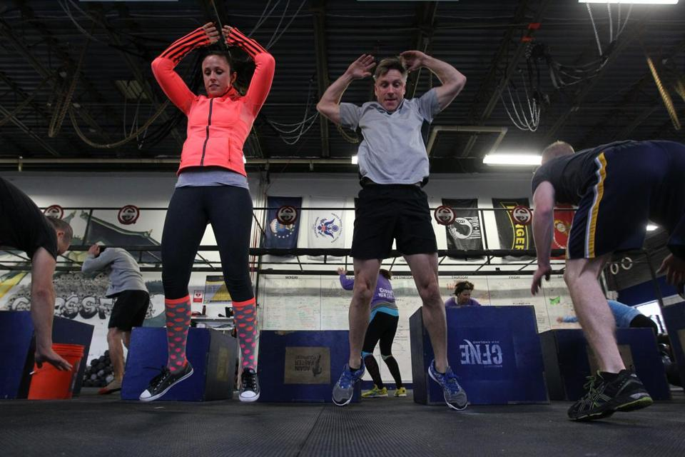 Maureen Becker and Dan Dougherty both of Natick, jump high as they do burpees during a warm up in a class at Crossfit New England.