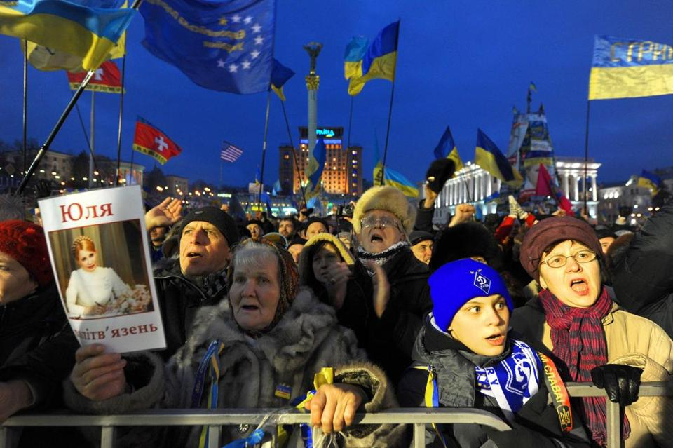 People shouted slogans and waved Ukrainian and European Union flags as a woman held a picture of jailed former Prime Minister Yulia Tymoshenko during a rally in Kiev.