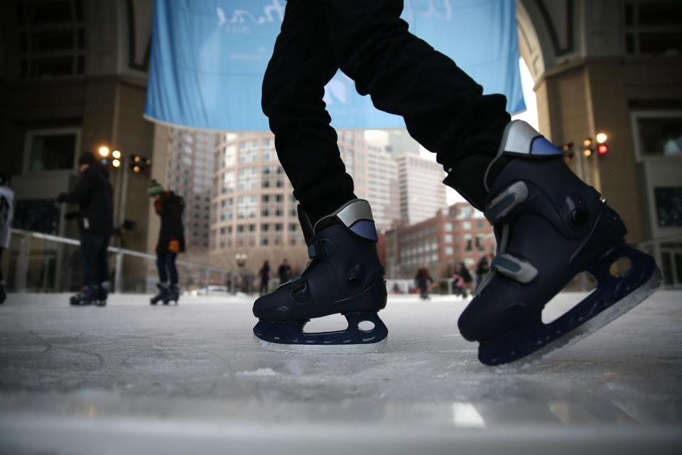 A skater glides along the rink at the Boston Harbor Hotel.