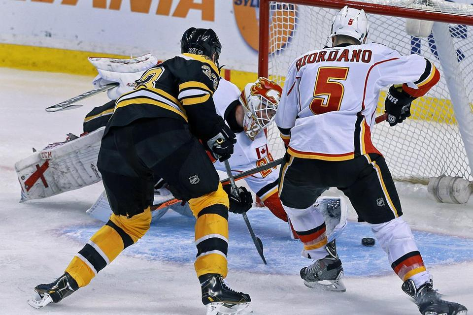 Bruin Zdeno Chara outmuscles Flames defenseman Mark Giordano to score the second of his two power-play goals, this one in the third period.
