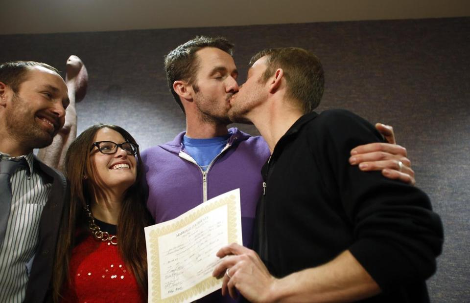 The first gay couple to be married in Utah, Michael Ferguson (second right) and his husband Seth Anderson (right), kissed after the ceremony.
