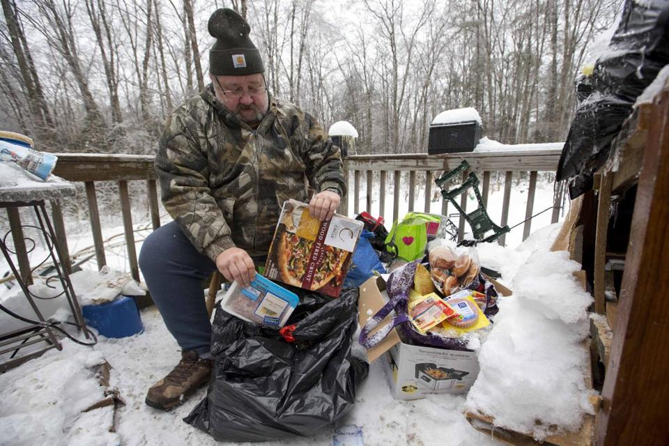 Tom Henson sorted through food he has been keeping cold on the deck of his home in Litchfield, Maine, where many people have been without power since Monday.