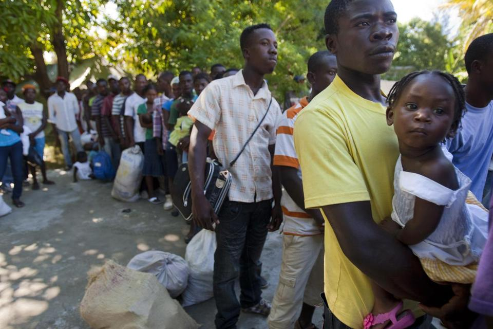 Louissien Pierra, 25, who was born in the Dominican Republic, held his 2-year-old daughter in November as they waited to board a bus to a Haitian town where they have family. Departures from the Dominican Republic to Haiti followed violence that erupted after a court ruling that could potentially revoke citizenship for residents of the Dominican Republic of Haitian descent.
