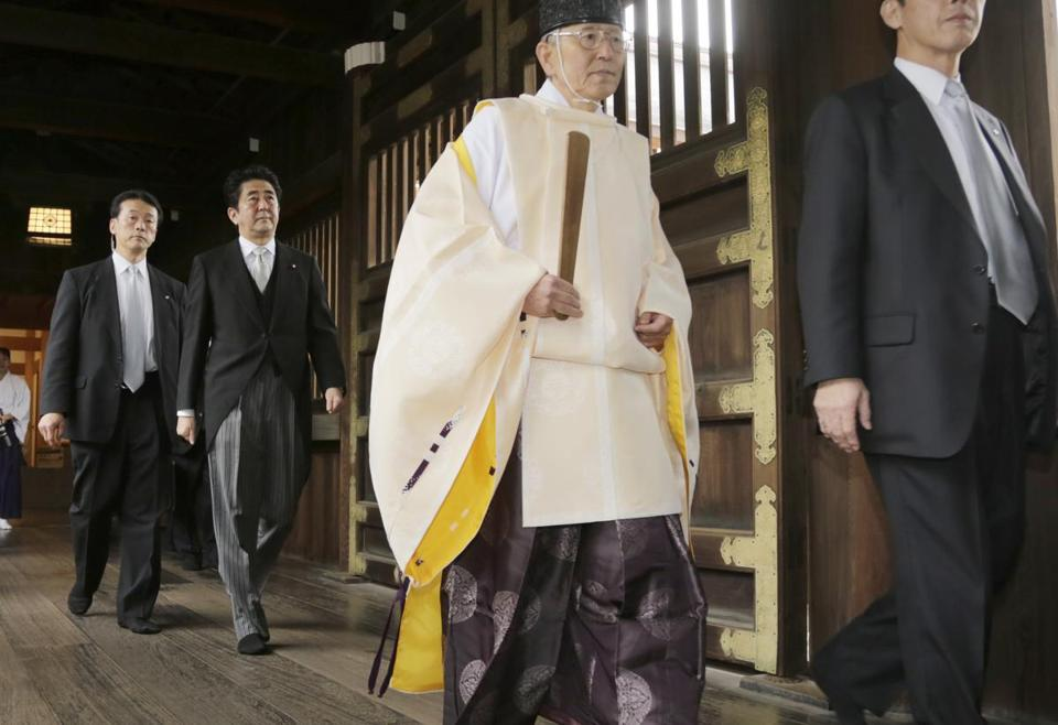 Japanese Prime Minister Shinzo Abe (second from left) followed a Shinto priest to at the Yasukuni Shrine during a visit in 2013.