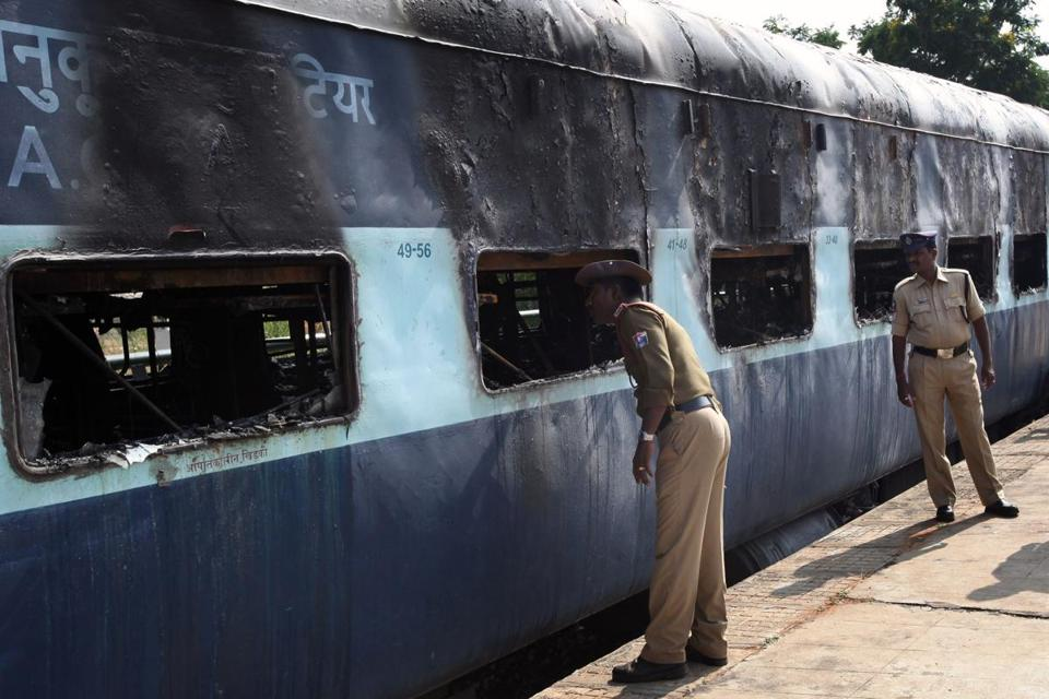 Indian policemen inspected a charred carriage after a fire engulfed the train.