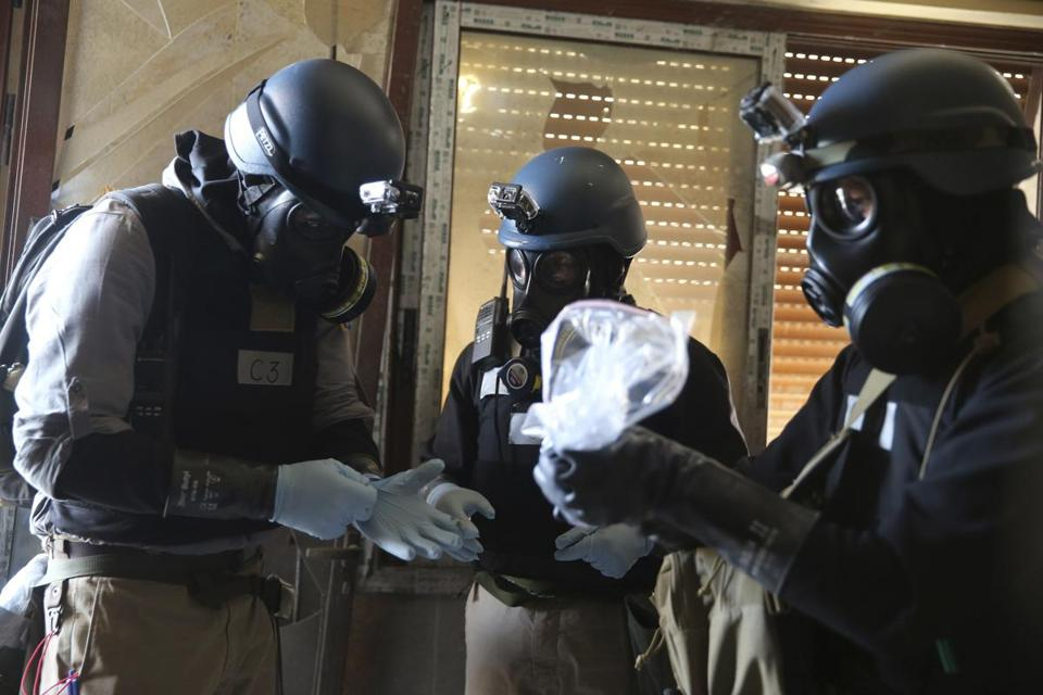 A UN chemical weapons expert held a plastic bag containing samples from one of the sites of a chemical weapons attack in a neighborhood in Damascus.