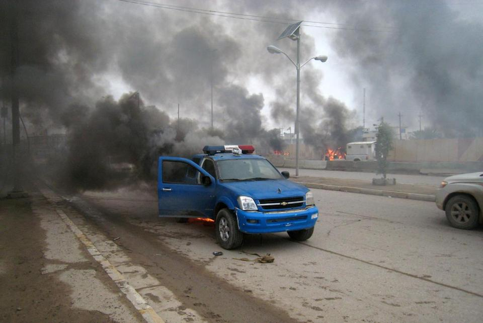 Iraqi forces battled insurgents for control of Fallujah and Ramadi, where smoke billowed from a police car Thursday.