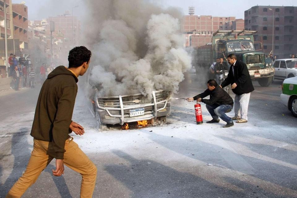 Two men tried to extinguish a police vehicle set on fire by Muslim Brotherhood supporters during protests in Cairo.