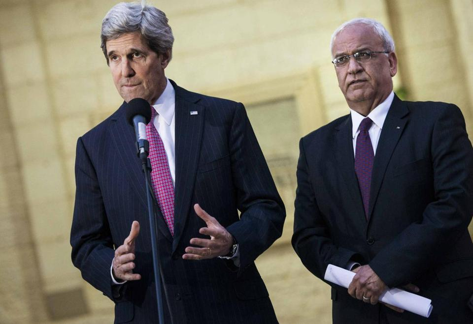 Palestinian negotiator Saeb Erekat listens as US Secretary of State John Kerry (left) speaks to the media after a meeting with Palestinian President Mahmoud Abbas i