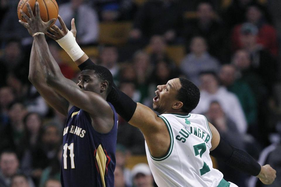 Jared Sullinger reached high as he tried to knock the ball free from Jrue Holiday's grip in the first quarter.