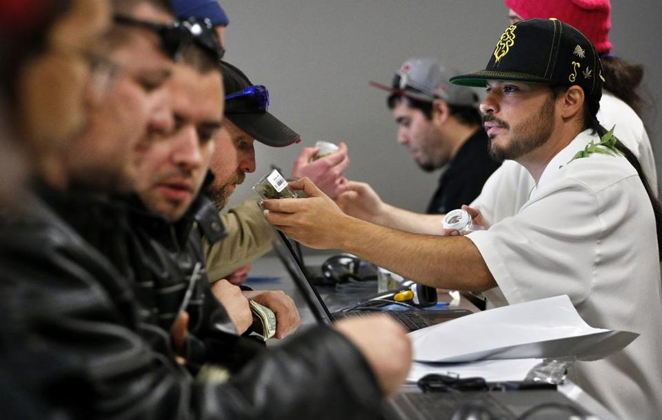Medicine Man marijuana store employee David Marlow helps a customer at the crowded sales counter on the store's opening day Jan. 1 in Denver.