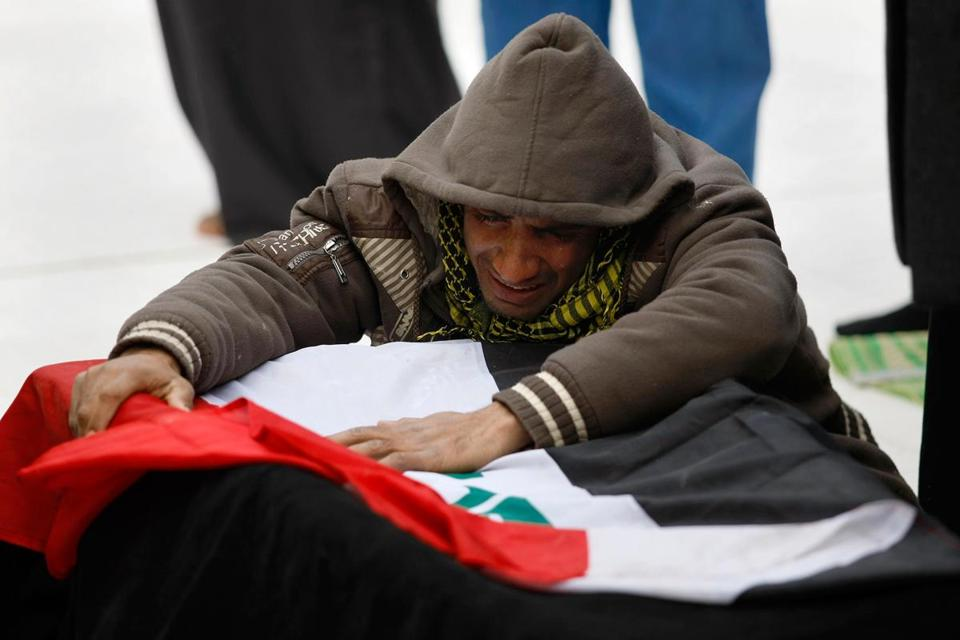 Mohammed Layth Ahmed wept over the coffin of his father, Layth, a soldier who was killed during clashes in Ramadi. His funeral was held in Najaf on Monday.