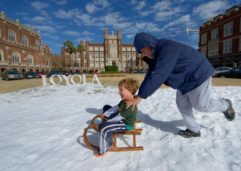 Armondo Hevia pushed his son, Emile, 7, at Loyola University in snow left over from a 12th Night snowball fight in New Orleans Tuesday. But below-freezing temperatures made life hard for some in the Big Easy.