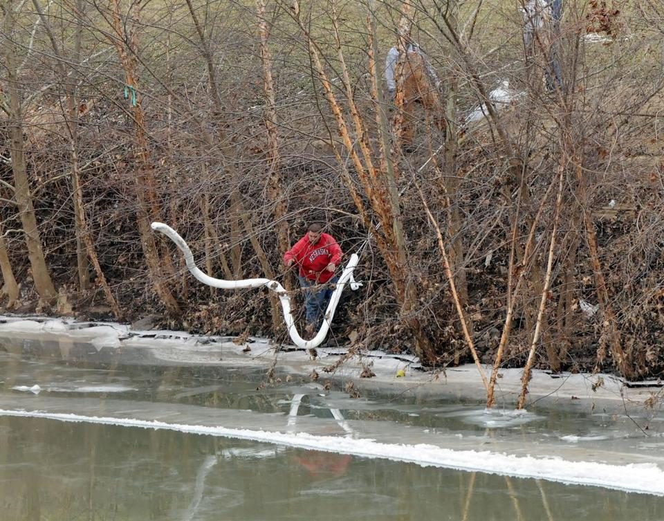 A Freedom Industries worker placed a boom in the Elk River at the site of a chemical leak in Charleston.
