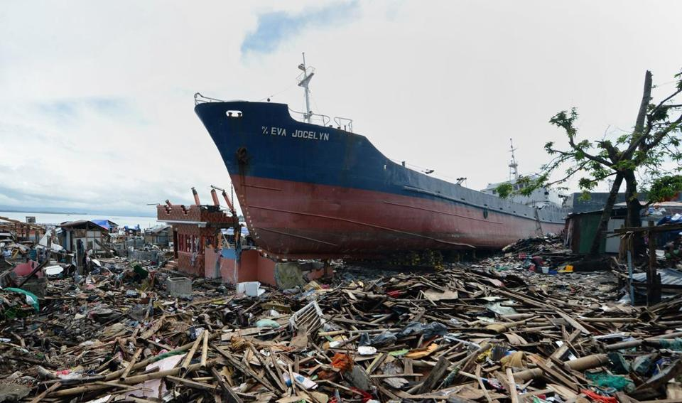 Weeks after the typhoon, a cargo ship still sat in debris in Tacloban, Philippines, where many people returned to ravaged areas seeking shelter in boats or freight containers.