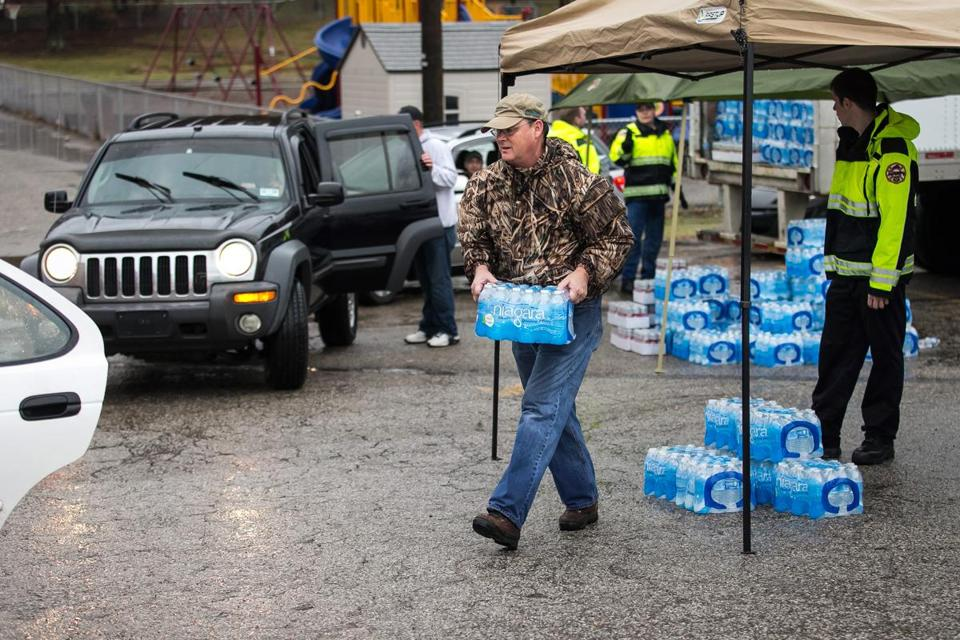 Members of a West Virginia volunteer fire department distributed bottled water to local residents on Saturday.
