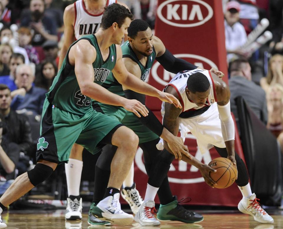 Kris Humphries (left) and Brandon Bass try to prevent Portland's Wesley Matthews from making a steal.