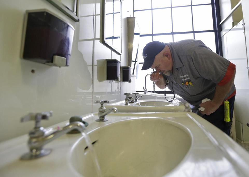 Al Jones of the West Virginia department of General Services tested the water as he flushed the faucet and opened a restroom on the first floor of the State Capitol in Charleston, West Virginia.