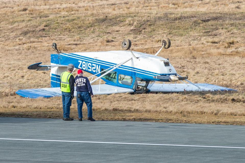 A small single-engine plane flipped over upon landing at the Beverly Municipal Airport.