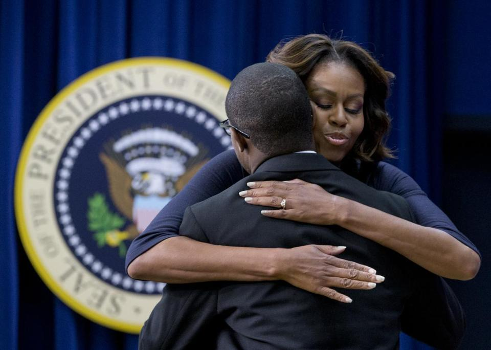 Michelle Obama embraced Bard College graduate Troy Simon at the White House meeting with college educators Thursday. Simon could not read until he was 14.