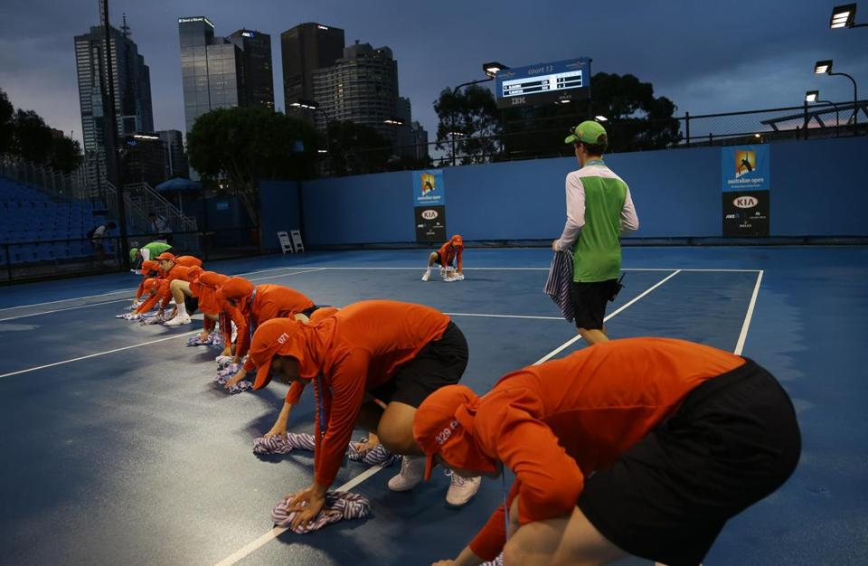 Ball boys dried the surface of an outside court after rain delayed play on the fourth day of the Australian Open.