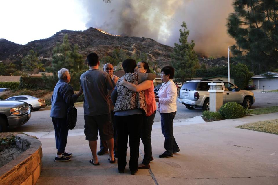 Family members comforted one another as they evacuated their home in Azusa, Calif., on Thursday. A wildfire, sparked by campers who have been arrested, burned at least 1,700 acres of the foothills of the San Gabriel Mountains.