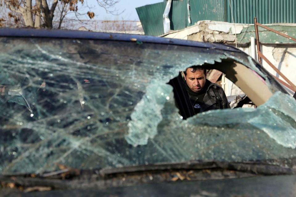 An Afghan security official examined the scene of a suicide bombing in Kabul by the Taliban that killed 21 people.