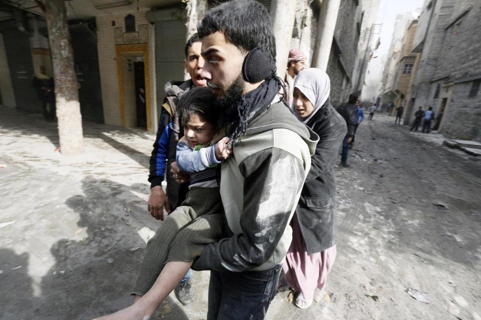 A man evacuated a child after an airstrike in the Al-Maysar neighborhood of Aleppo, Syria, on Sunday.