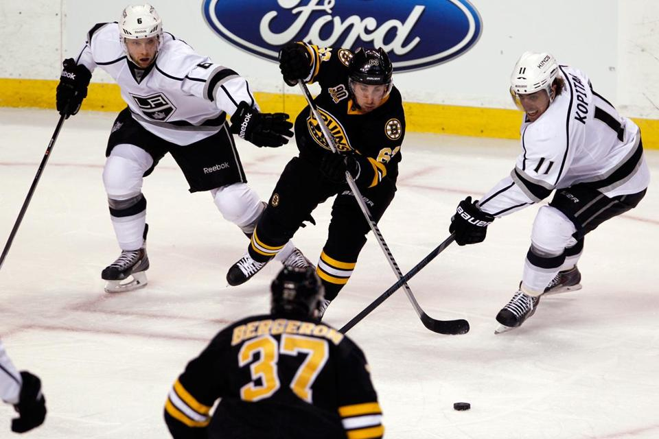 Brad Marchand was in the middle of things again for the Bruins. Here he stickhandles between Kings Jake Muzzin (left) and Anze Kopitar.