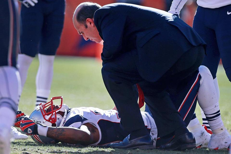 Dr. Thomas Gill checks on Patriots cornerback Aqib Talib after Talib was leveled on a pick play by Broncos wide receiver WesWelker in the second quarter of Sunday's game.