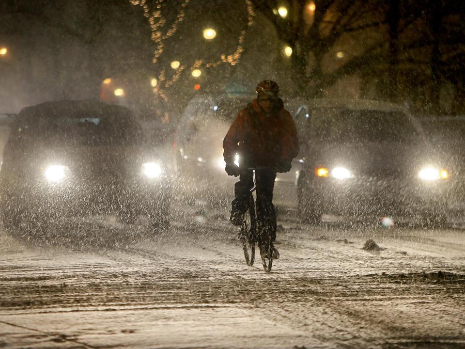 As the snow began to accumulate Tuesday night, a bicycle commuter pedaled through Coolidge Corner in Brookline.