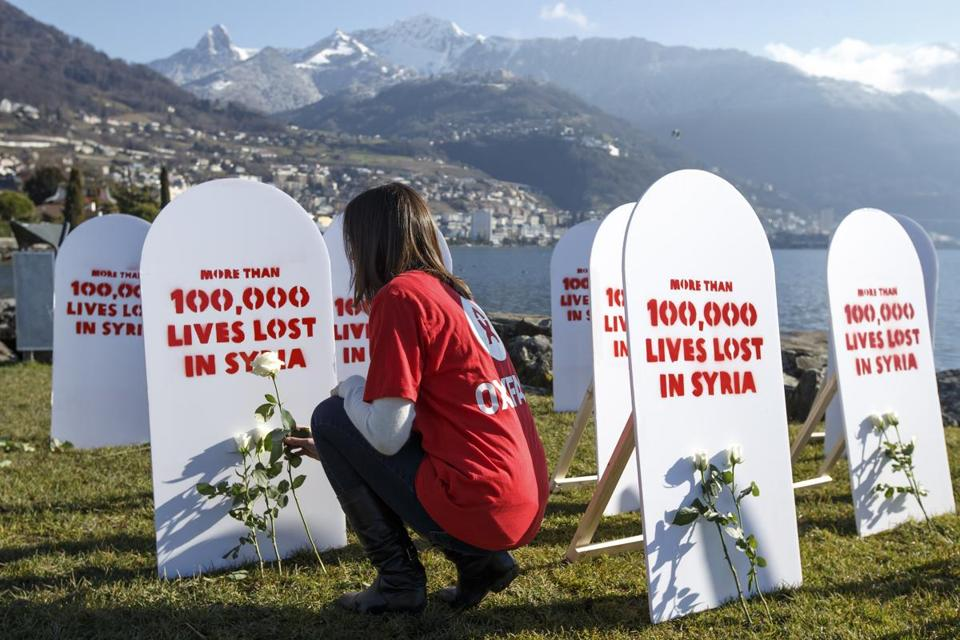 A member of Oxfam placed roses on symbolic gravestones at the opening of the Syria talks in Montreux.