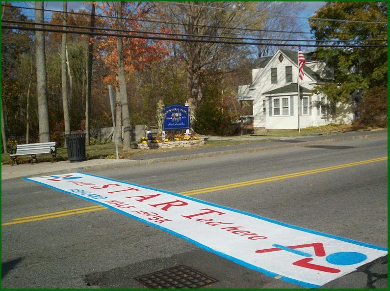 A marker recalling the original Boston Marathon starting line stretches across  Route 135 in Ashland.