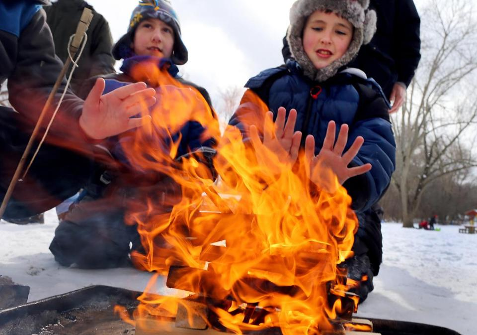 Scouts Joey McCoy, 10, and Tom Davidson, 9, kept warm by a fire they lit at Endicott Park in Danvers at the annual Klondike Derby, where about 350 youths camped out and competed in survival challenges for three days.