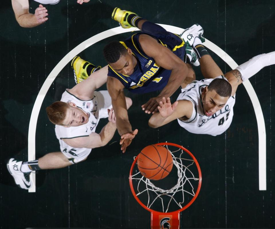 From left: Michigan State's Russell Byrd, Michigan's Glenn Robinson III, and Michigan State's Denzel Valentine, reached for a rebound during the second half.
