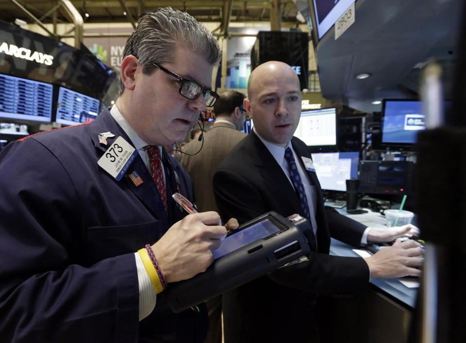 Trader John Panin (left), and specialist Jay Woods worked on the floor of the New York Stock Exchange on Tuesday.