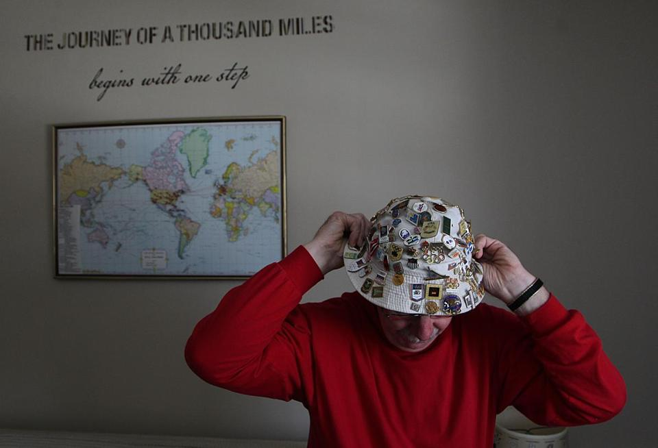 Bob Boehm of Lowell dons his hat adorned with Olympic pins that he wears to Olympic Games and collector shows. Boehm has accumulated some 5,000 pins and other Olympic memorabilia over the past 40 years.  The map on the wall marks the 13 Olympic Games that he has attended. He did not go to Sochi as he had planned due to personal reasons.