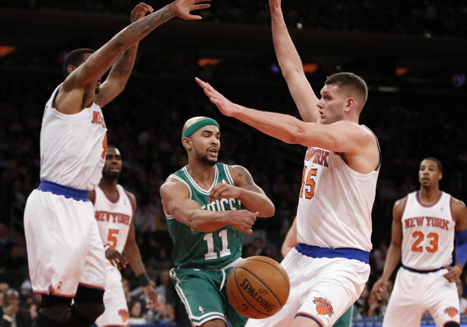 Celtics guard Jerryd Bayless was defended by Jeremy Tyler and Cole Aldrich of the Knicks.