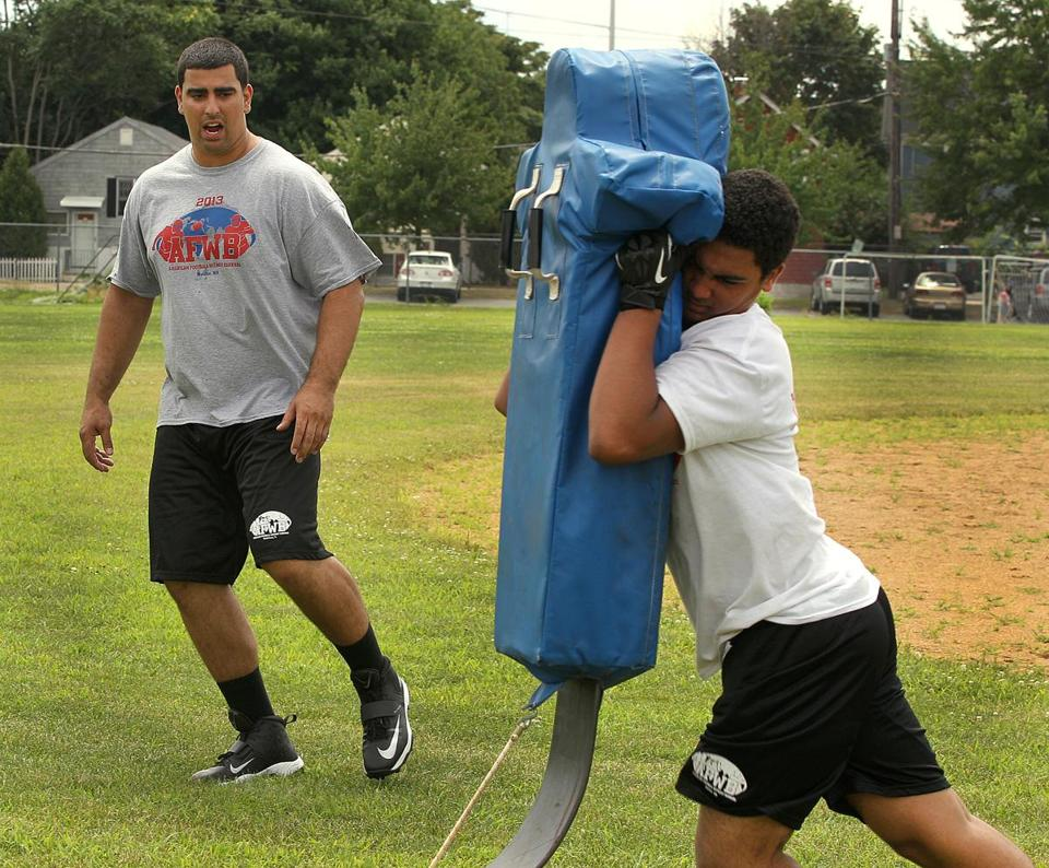 Breno Giacomini worked with Malden High School's Gabriel Padilla during a football skills camp in Malden last summer. Giacomini, a Malden High School product, will suit up for the Seahawks in Sunday's Super Bowl.