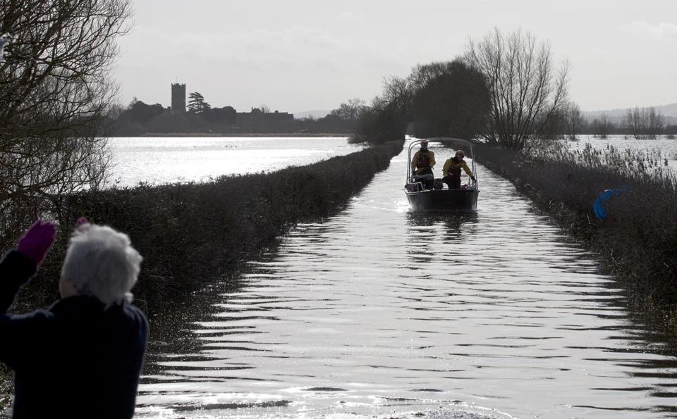 An emergency services boat navigated flooded roads on the Somerset Levels in southwest England.