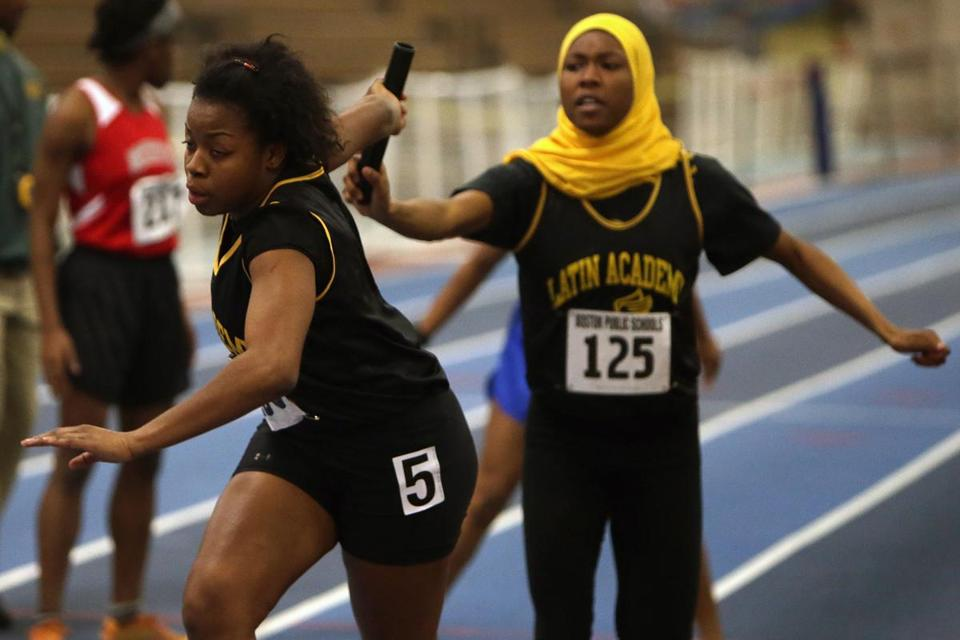 Latin Academy's DiAndrea Galloway takes the baton from Imani Presley during the Dragons' victorious 4 x 200 relay.