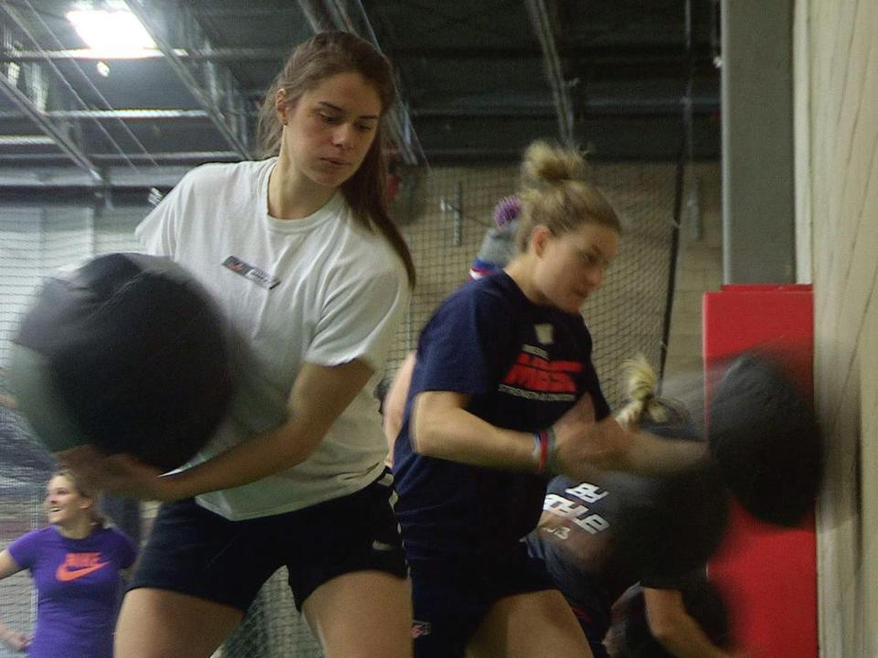 US Olympic women's hockey player Josephine Pucci (front) works the medicine ball at Mike Boyle's fitness center.