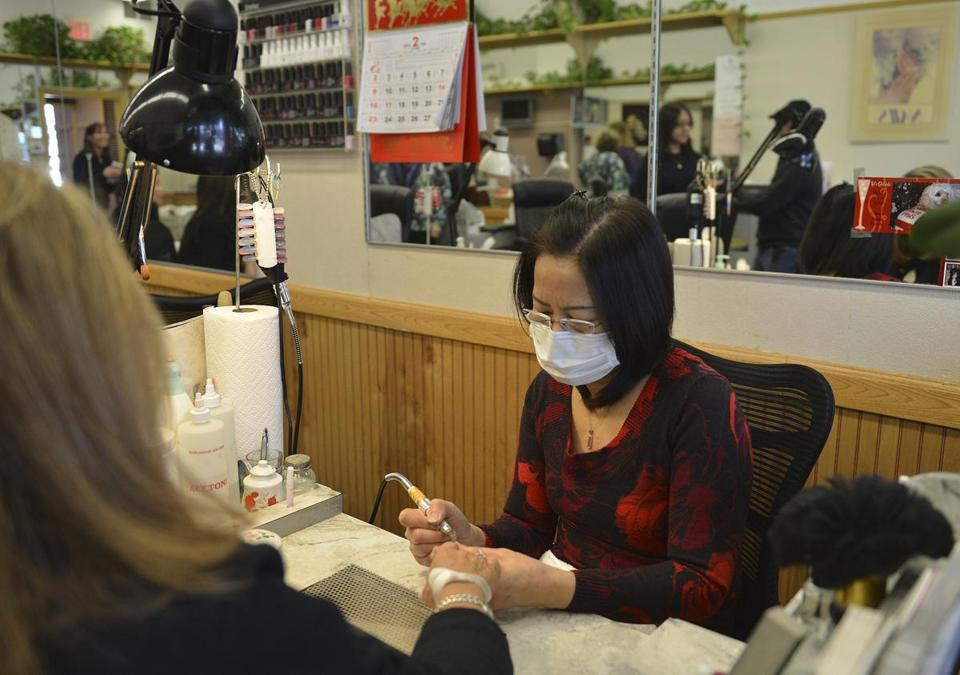 Chi Duong, co-owner of Top Line Nails in Needham, dons a mask at a public health official's urging as she worked on a client's nails.